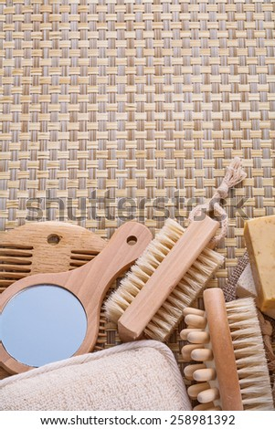 mirror hairbrush nail brush massager soap on wicker background with copyspace  - stock photo