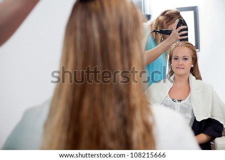 Mirror reflection of beautician drying long blond hair with hair dryer at parlor - stock photo