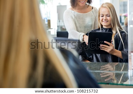 Mirror reflection of female customer holding digital tablet with hairdresser standing behind her - stock photo