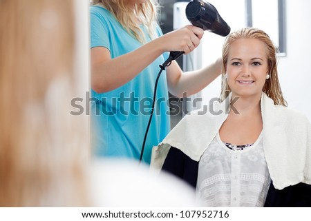 Mirror reflection of hairdresser drying long blond hair with blow dryer at parlor - stock photo