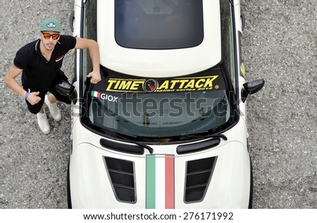 MISANO, ITALY - MAY 1, 2015: Boy with cap and sunglassess laying next to her sports car. View from above of a man with her sportive race car on Misano at May 1, 2015 - stock photo
