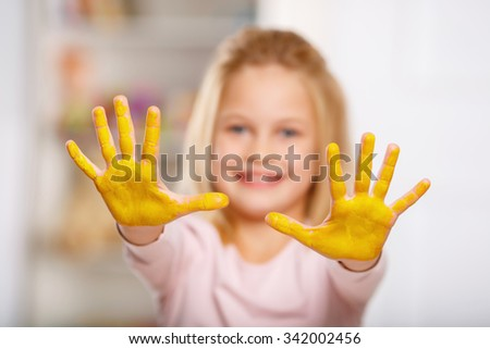 Mischief managed. Cheerful little girl demonstrating her palms covered in yellow gouache.  - stock photo