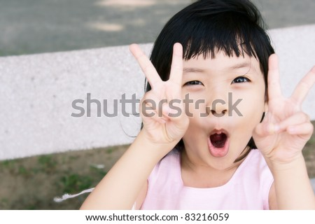 Mischievous pink girl in a victory pose. - stock photo