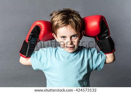 mischievous young boy with red hair and freckles holding his boxing gloves up to win a sporty competition, grey background studio