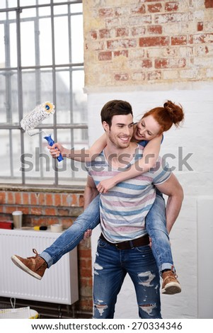 Mischievous young woman riding piggy back on her husbands back as she brandishes a paint brush full of white paint while renovating the apartment - stock photo
