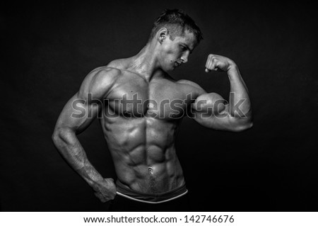 Miscled male model in studio - stock photo