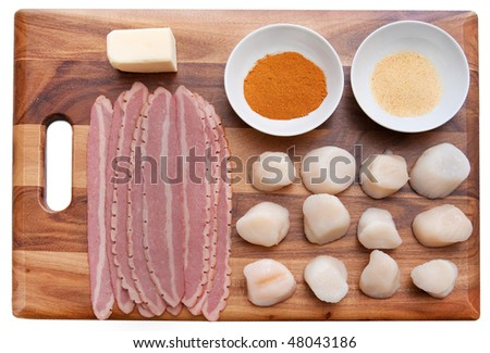 mise en place ingredients for making bacon wrapped scallops laid out neatly on a cutting board before cooking - stock photo