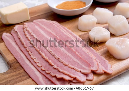mise en place on a wooden cutting board for a batch of bacon wrapped scallops before being cooked - stock photo