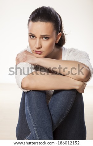 miserable and sad young woman sitting on a white background