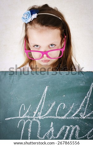 Miserable girl standing behind the blackboard - stock photo
