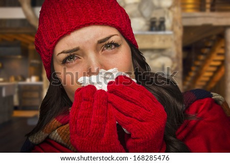 Miserable Sick Woman Inside Log Cabin Blowing Her Sore Nose With Tissue. - stock photo