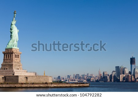 Miss Liberty with Blue Sky and Manhattan Skyline - stock photo