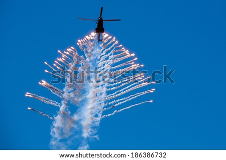 missiles being fired by a military helicopter - stock photo