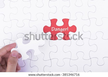 Missing a piece of puzzle in the center, red space with word DANGER, business and financial concept. - stock photo
