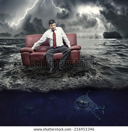 Missing a stormy sea of sharks with a man floating on a sofa