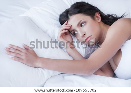 Missing him. Depressed young women lying on the bed and holding hand on pillow - stock photo