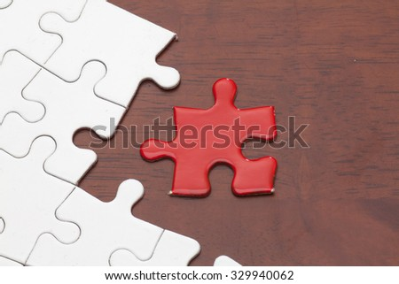 Missing jigsaw puzzle piece, business concept for completing the final puzzle piece on wood - stock photo