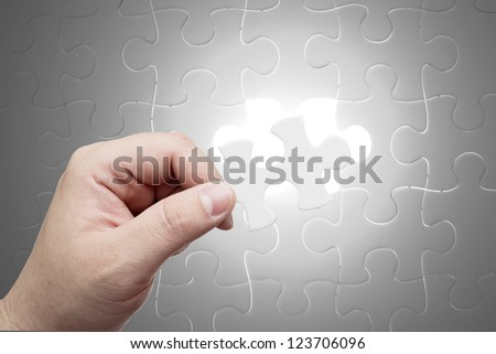 Missing jigsaw puzzle piece with light glow, business concept for key completion for business success - stock photo