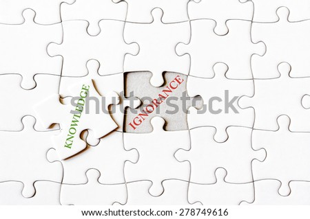 Missing jigsaw puzzle piece with word KNOWLEDGE, covering text IGNORANCE. Business concept image for completing the final puzzle piece.