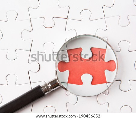 Missing jigsaw puzzle pieces revealing a red surface layer with a magnifying glass