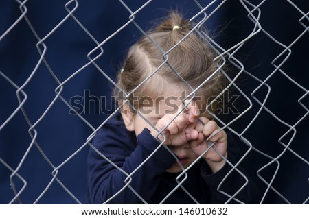 Missing kidnapped, abused, hostage, victim girl alone in emotional stress and pain, afraid, restricted, trapped, call for help, struggle, terrified, threaten, behind a fence locked in a cage cell  - stock photo