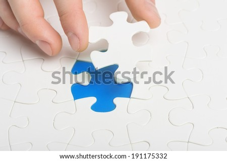 Missing Piece. A hand fitting the last piece of puzzle in place
