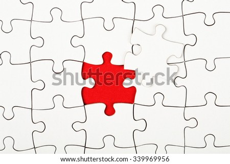 Missing piece in a puzzle on red background, business conception - stock photo