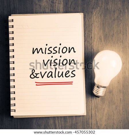 Mission Vision and Values as memo on notebook with glowing light bulb