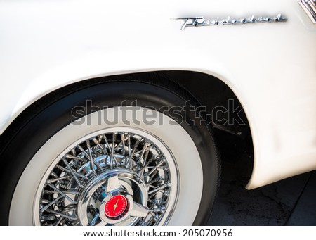 """MISSISSAUGA, CANADA - JULY 6 2014: A Ford Thunderbird emblem and front whitewall tire on a classic white model. As seen at """"Classics on the Square"""", a car show in Mississauga, Canada on July 6, 2014. - stock photo"""