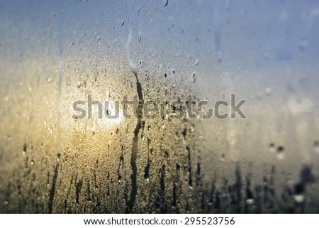 Mist and raindrops on glass pane after a night of rain - stock photo
