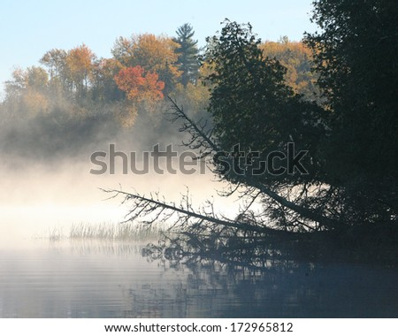 Mist on a northern lake - stock photo