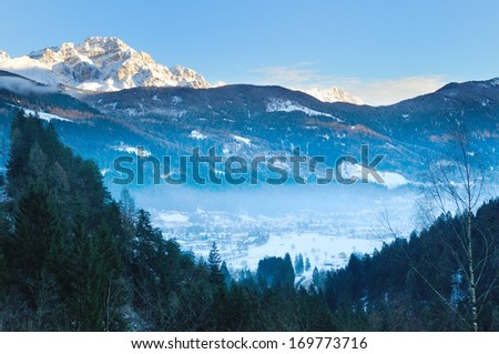 mist over Pinzolo (TN) Italy ski area at sunset - stock photo
