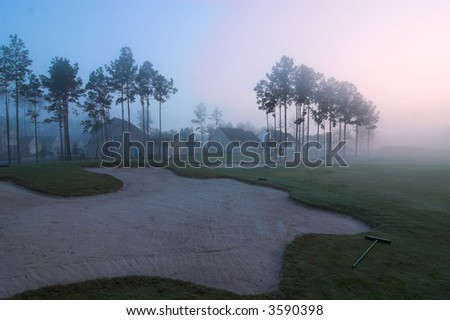misty golf course sand trap with homes in background, predawn - stock photo