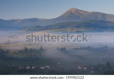 Misty morning in the mountains. View of the village under the fog. Carpathian mountains, Ukraine, Europe - stock photo