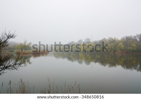 Misty Morning Lake. A thick early morning fog on this lake. - stock photo