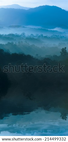 Misty morning of hilly area with ray of light - digital composite,  water reflection and ripple effects.  - stock photo