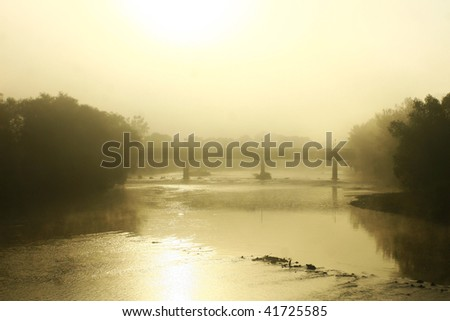 Misty morning river with bridge. - stock photo