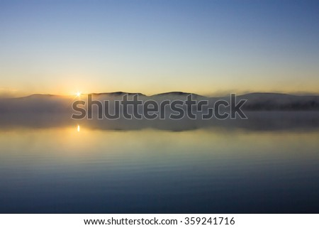 misty morning; the sun rises over the lake with fog; mist rising above the water - stock photo