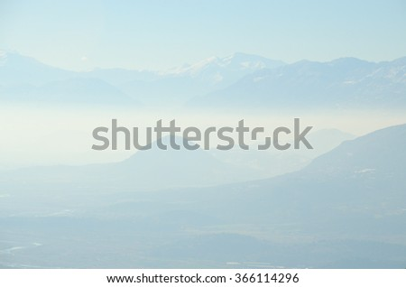 Misty mountains landscape. Light blue universal nature background. Beautiful winter mountains in Greece.
