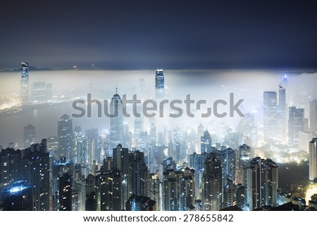 Misty night view of Victoria harbor in Hong Kong city - stock photo