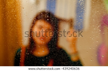 misty reflection of girl in the mirror with water droplets. combing her hair - stock photo