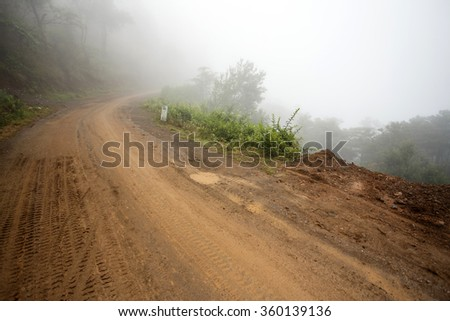 Misty Road Leading Through Chin State Mountains, Myanmar - stock photo