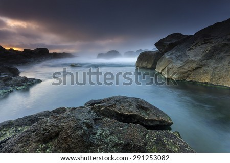 Misty seascape sunset on south coast of Iceland/ Misty ocean sunset in Iceland - stock photo