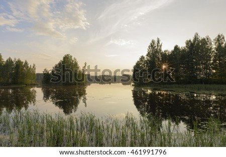 Misty summer evening scenery by the lake