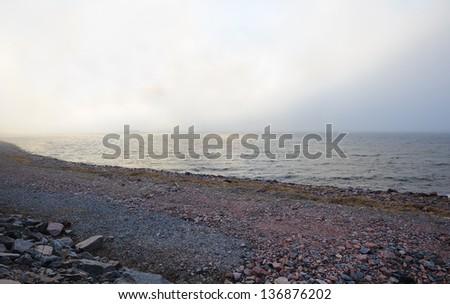 Misty view of The Baltic sea granite shoreline - stock photo