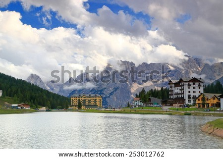 Misurina lake with large hotels and distant range of Sorapis under large clouds, Dolomite Alps, Italy - stock photo