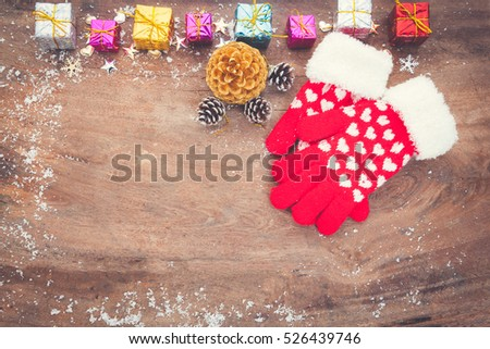 Mitten with Christmas decoration on wooden board. Winter decoration