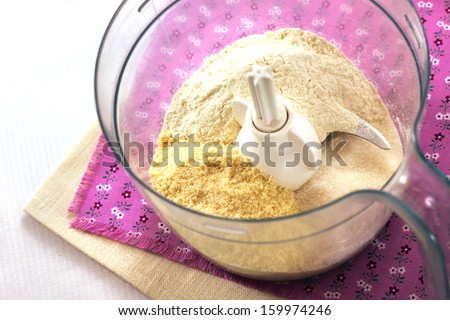 Mix for making shortcrust pastry in food processor  in process of cooking Almond tart with raspberries and white chocolate - stock photo