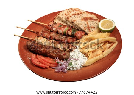 mix grill of skewers served on a plate with pita fries and tzatziki sauce - stock photo