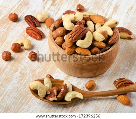 Mix nuts on a wooden table. Selective focus